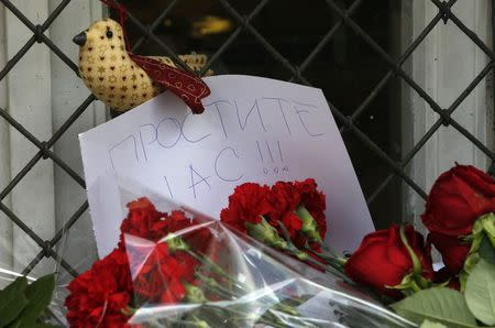 "A note is seen with flowers placed outside the Dutch embassy in Moscow July 18, 2014. The note reads, ""Forgive us!!!"" REUTERS/Sergei Karpukhin"