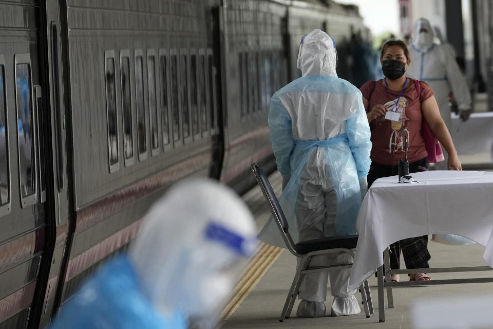 A health worker talks with a woman, who is among a group of people infected with COVID-19, as she arrived at Rangsit train station in Pathum Thani Province, Thailand, Tuesday, July 27, 2021. Thai authorities began transporting some people who have tested positive with the coronavirus from Bangkok to their hometowns on Tuesday for isolation and treatment, to alleviate the burden on the capital's overwhelmed medical system. (AP Photo/Sakchai Lalit)
