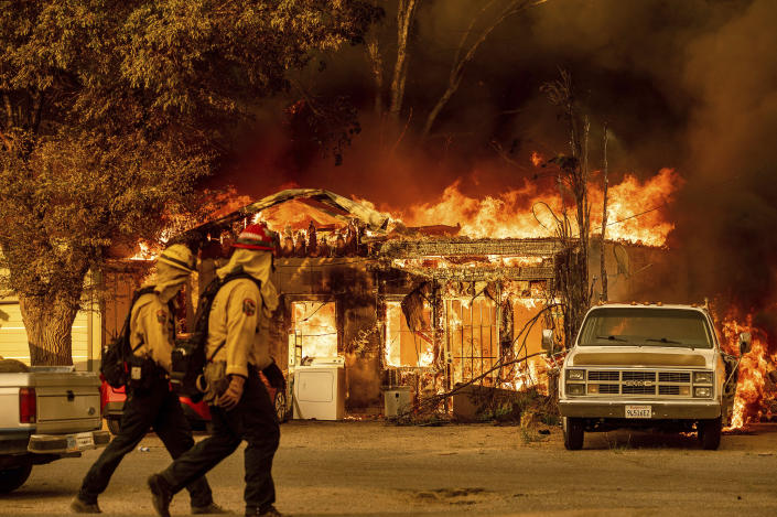 Firefighters pass a burning home as the Sugar Fire, part of the Beckwourth Complex Fire, tears through Doyle, Calif., on Saturday, July 10, 2021. Pushed by heavy winds, the fire came out of the hills and destroyed multiple residences in central Doyle. (AP Photo/Noah Berger)