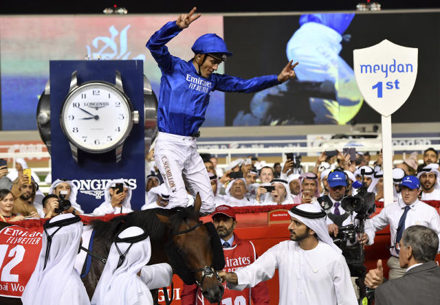 Jockey Christophe Soumillon performs a flying dismount while Dubai Crown Prince Sheikh Hamdan bin Mohammed Al Maktoum holds Thunder Snow after winning for the second time in a row the $12 million Group 1 Dubai World Cup over 2000m in Dubai, United Arab Emirates, Saturday, March 30, 2019. Thunder Snow is the only horse that won two Dubai World Cups in consecutive years. (AP Photo/Martin Dokoupil)
