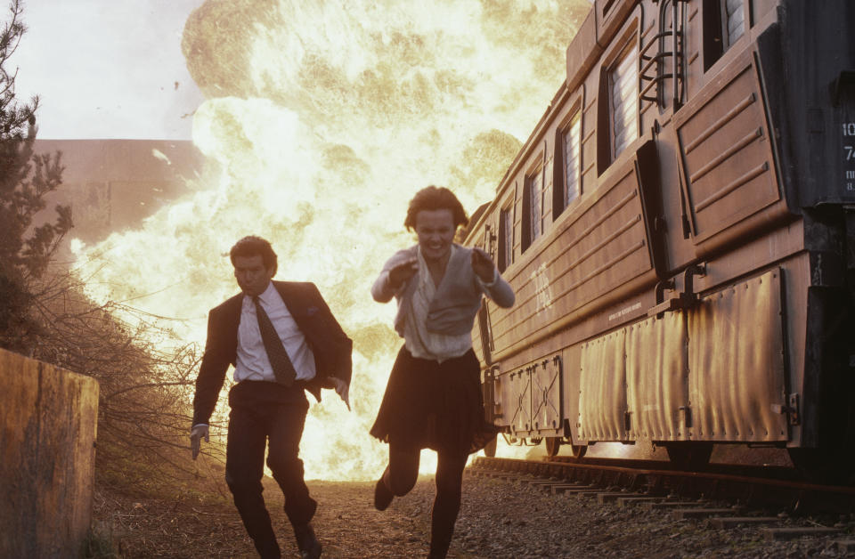 Polish actress Izabella Scorupco and Irish actor Pierce Brosnan flee from an exploding train in a scene from the James Bond film 'GoldenEye', 1995. (Photo by Keith Hamshere/Getty Images)