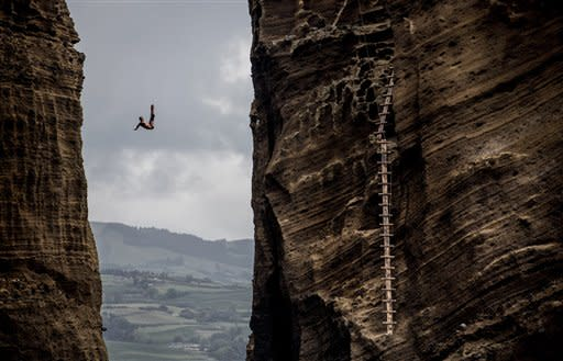Artem Silchenko of Russia dives from the 27.5 metre rock during the third stop of the Red Bull Cliff Diving World Series in Islet Vila Franca do Campo, Azores, Portugal, Saturday July 21, 2012. Artem Silchenko of Russia won the round but Duque takes the overall lead after a second place finish Saturday. (AP Photo / Dean Treml via Romina Amato/Red Bull)