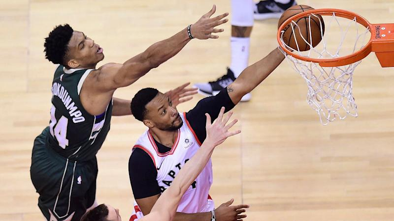 Toronto Raptors forward Norman Powell (24) scores past Milwaukee Bucks forward Giannis Antetokounmpo (34) and guard Pat Connaughton (24) during first half NBA Eastern Conference finals basketball action in Toronto on Sunday, May 19, 2019. THE CANADIAN PRESS/Frank Gunn