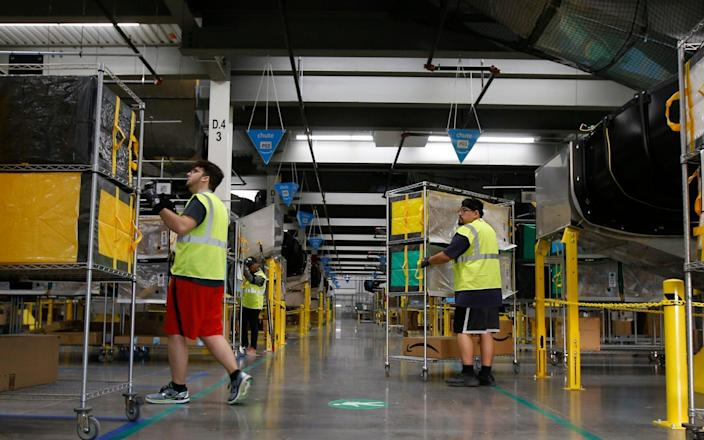 Amazon workers move containers to delivery trucks at an Amazon warehouse facility in Goodyear, Ariz. Starting Monday, Aug. 9, 2021, Amazon will be requiring all of its 900,000 U.S. warehouse workers to wear masks indoors, regardless of their vaccination status. The move follows steps by a slew of other retailers, including Walmart and Target, to mandate masks for their workers. In many of those cases the mandates apply to workers in locations of substantial COVID-19 transmission - AP