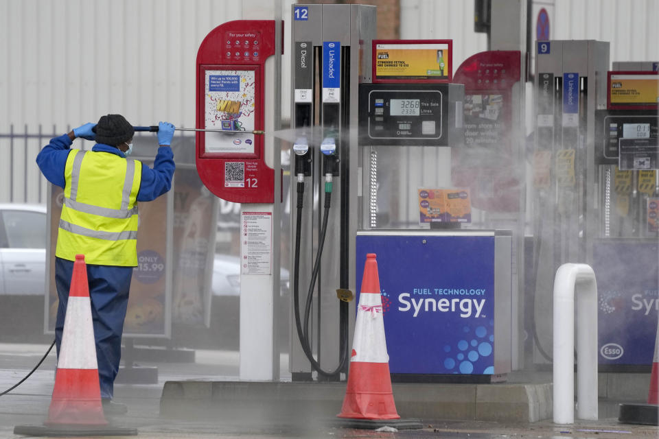 An employee cleans fuel pumps at a closed petrol station in London, Thursday, Sept. 30, 2021. Many gas stations around Britain have shut down in the past five days after running out of fuel, a situation exacerbated by panic buying among some motorists. Long lines of vehicles formed at pumps that were still open, blocking roads and causing traffic chaos. Some drivers have had to endure hourslong waits to fill up. (AP Photo/Frank Augstein)