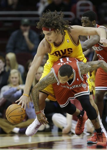 Cleveland Cavaliers' Anderson Varejao, from Brazil, fights for a loose ball with Milwaukee Bucks' Monta Ellis (11) in the first quarter of an NBA basketball game on Friday, Dec. 14, 2012, in Cleveland. (AP Photo/Mark Duncan)