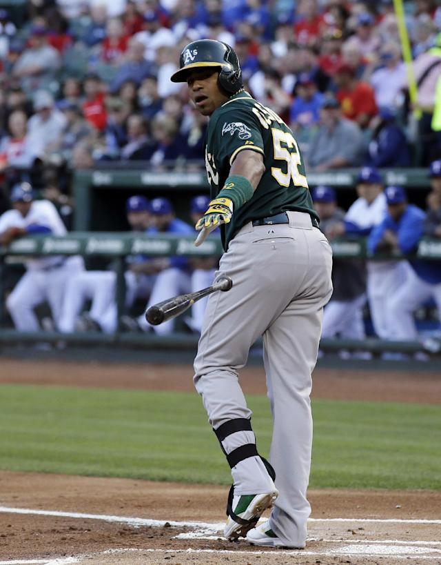 Oakland Athletics' Yoenis Cespedes tosses the bat after earning a walk against Texas Rangers' Martin Perez in the first inning of a baseball game, Tuesday, April 29, 2014, in Arlington, Texas. (AP Photo/Tony Gutierrez)