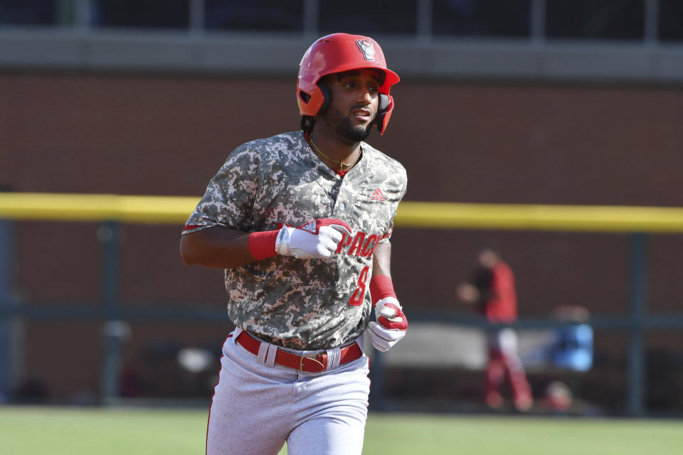 North Carolina State baserunner Jose Torres (8) rounds the basses after hitting a home run against Arkansas in the second inning of an NCAA college baseball super regional game Friday, June 11, 2021, in Fayetteville, Ark. (AP Photo/Michael Woods)