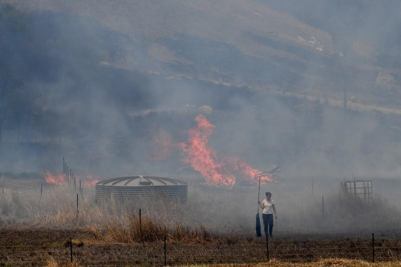 A resident fights a grass fire in the Hillville area near Taree