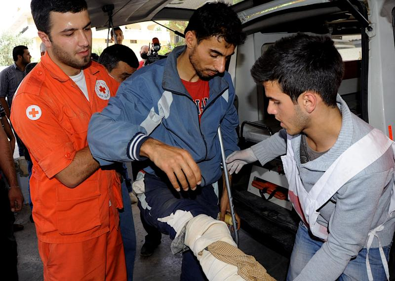 FILE - In this Saturday, June 8, 2013 file photo, members from the Lebanese Red Cross help a Syrian man who was wounded in Qusair, Syria, during battles between the rebels and the Syrian government forces, at a hospital in the Bekaa Valley, east of Beirut, Lebanon. Syrian rebels' defeat in Qusair cost them more than a strategic location, it has also left a battered spirit and deep frustration. Over the course of a year, rebels holding the town had heavily fortified it with tunnels, mine fields, and booby traps and when the regime assault came they fought back ferociously. But in the end they were outgunned and outnumbered, and were forced into a harrowing, crushing flight from the town. (AP Photo, File)