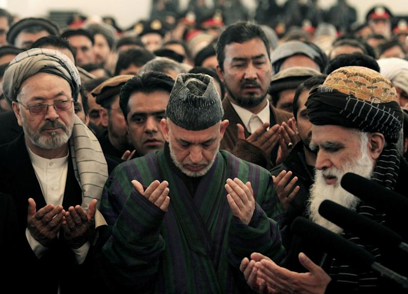 Afghan President Hamid Karzai, center, prays during the funeral procession of Afghanistan's influential Vice President Mohammad Qasim Fahim in Kabul, Afghanistan, Tuesday, March 11, 2014. Fahim, a leading commander in the alliance that fought the Taliban who was later accused with other warlords of targeting civilian areas during the country's civil war, died on Sunday, March 9, 2014. He was 57. (AP Photo/Rahmat Gul)
