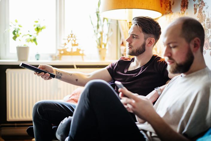 Couple relaxing at home together, watching tv and using a smartphone. (Getty)