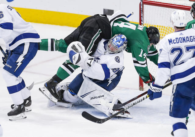 Dallas Stars forward Jamie Benn (14) falls onto Tampa Bay Lightning goaltender Andrei Vasilevskiy (88) during the second period of an NHL hockey game, Tuesday, Jan. 15, 2019, in Dallas. Benn was penalized for goaltender interference on the play. (AP Photo/Brandon Wade)