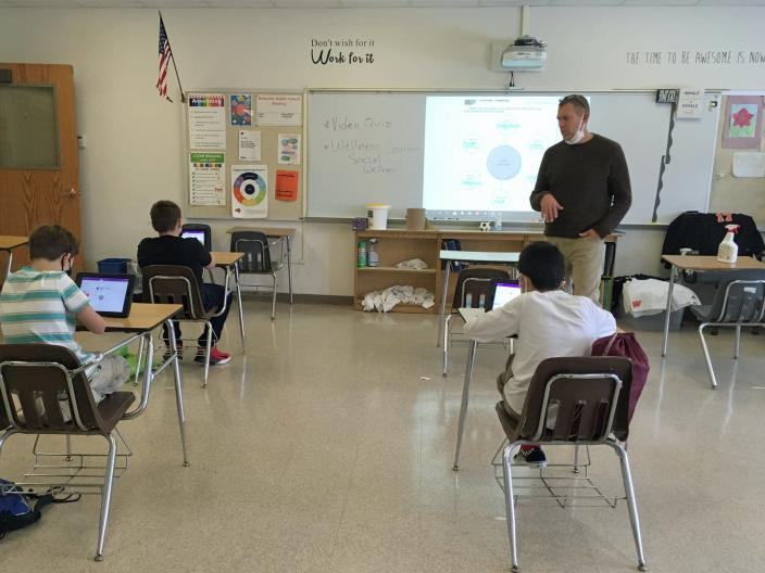 A teacher wearing a mask conducts his class while his students sit using iPads.