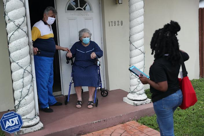 A woman speaks with two people on their doorstep.