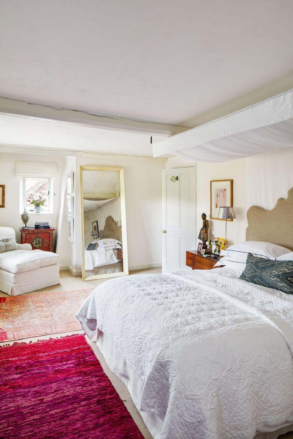 """<p>""""I wanted a very calm bedroom, so we painted everything in Christophe's White from <a href=""""https://www.francescaspaint.com/index.php"""" rel=""""nofollow noopener"""" target=""""_blank"""" data-ylk=""""slk:Francesca's Paints"""" class=""""link rapid-noclick-resp"""">Francesca's Paints</a>. I have always used her eco-friendly lime washes so the old walls of our house can breathe. Then I added a very bright raspberry old Berber rug we brought back from Morocco, which is such a joy. I can't resist colour.""""</p>"""
