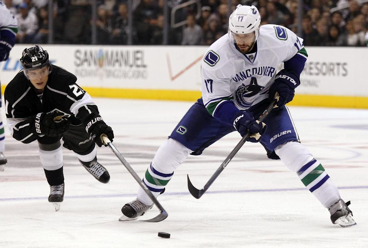 Los Angeles Kings right wing Matt Frattin, left, battles Vancouver Canucks center Ryan Kesler (17) for the puck during the third period of an NHL hockey game Saturday, Jan. 4, 2014, in Los Angeles. Kings won 3-1.  (AP Photo/Alex Gallardo)