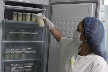 Nurse examines bottles of breast milk kept in a fridge on the first day of donation at a hospital in Medellin