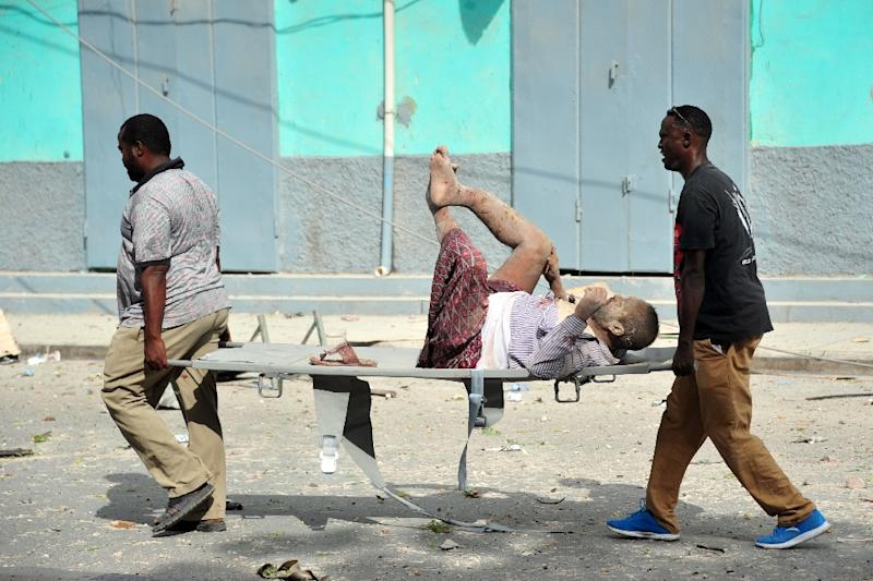 Residents carry an injured man wounded during a complex car bomb attack targeting a Mogadishu hotel on January 25, 2017 (AFP Photo/MOHAMED ABDIWAHAB)