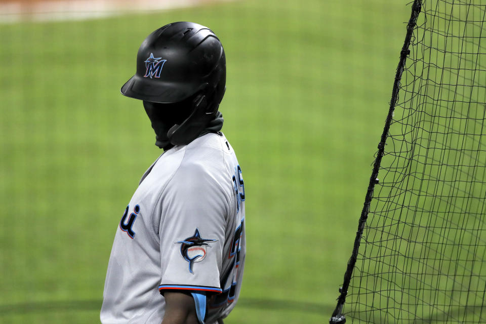 Miami Marlins' Lewis Brinson wears a face mask to protect against COVID-19 while standing at the on deck circle during the sixth inning of a baseball game against the Baltimore Orioles, Tuesday, Aug. 4, 2020, in Baltimore. (AP Photo/Julio Cortez)