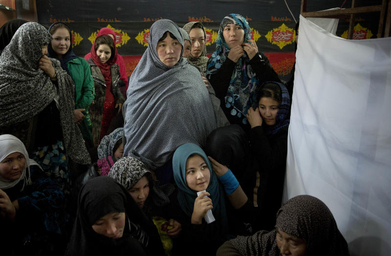 In this Saturday, Nov. 9, 2013 photo, Afghan women line up to have their picture taken to register for the upcoming Afghan elections in a mosque, used as a mobile voter registration place in Kabul, Afghanistan. Getting Afghan women voter cards has proven a challenge for the Independent Election Commission (IEC), due to strict traditional values and the lack of female registration employees.(AP Photo/Anja Niedringhaus)