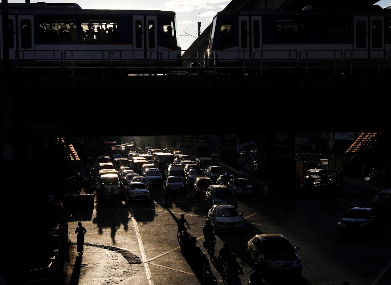 Commuters and motorists are silhouetted on a main thoroughfare in Cubao, metro Manila, Philippines January 12, 2018.   REUTERS/Dondi Tawatao
