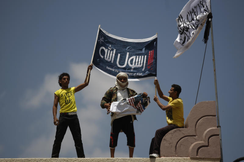 """A Yemeni protestor, center, destroys an American flag pulled down as other hold a banner in Arabic that reads, """"any one but you God's prophet"""" at the U.S. Embassy compound during a protest about a film ridiculing Islam's Prophet Muhammad, in Sanaa, Yemen, Thursday, Sept. 13, 2012. Dozens of protesters gather in front of the US Embassy in Sanaa to protest against the American film """"The Innocence of Muslims"""" deemed blasphemous and Islamophobic. (AP Photo/Hani Mohammed)"""