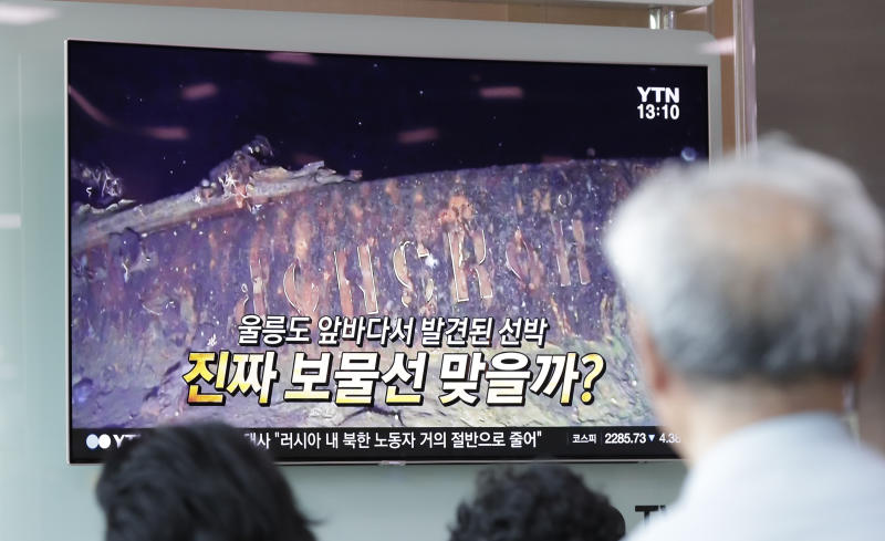 "People watch a TV screen showing the news program reporting about a sunken Russian warship at the Seoul Railway Station in Seoul, South Korea, Thursday, July 19, 2018. A South Korean company's claim to have found a sunken Russian warship has triggered investor frenzy amid unconfirmed rumors that the ship was carrying 200 tons of gold when it sank in 1905. The letters read ""Is it real treasure ship?"" (AP Photo/Lee Jin-man)"