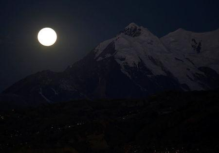 The  moon is seen near the Illimani mountain during a full lunar eclipse in La Paz, Bolivia, July 27, 2018. REUTERS/David Mercado