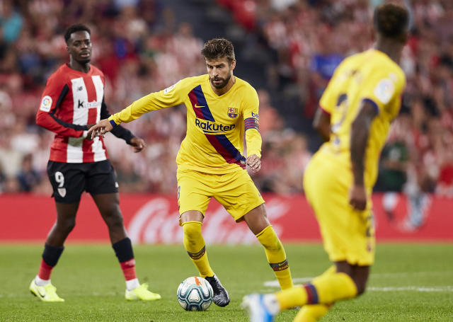 Barcelona's Gerard Pique, center, controls the ball during the Spanish La Liga soccer match between Athletic Bilbao and FC Barcelona at San Mames stadium in Bilbao, northern Spain, Friday, Aug. 16, 2019. (AP Photo/Ion Alcoba Beitia)