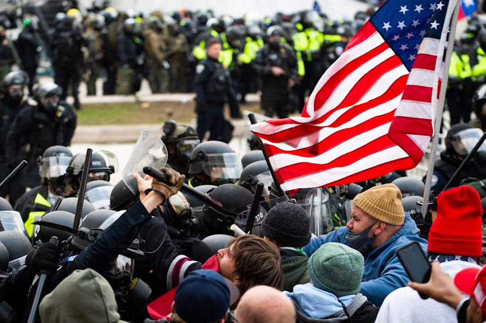 Supporters of US President Donald Trump fight with riot police outside the Capitol building on January 6, 2021 in Washington, DC (AFP via Getty Images)