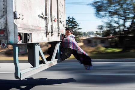 Migrant Javier Gomez, from Honduras, takes a lift in the back of a truck during his journey towards the United States, in Mexico City, Mexico, January 31, 2019. REUTERS/Alexandre Meneghini