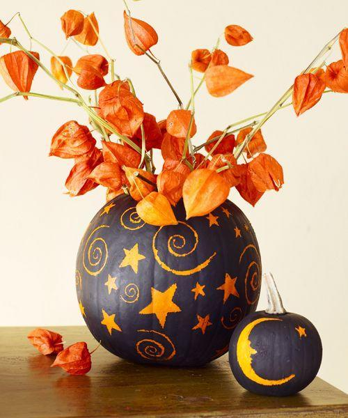 <p>These vases do require a knife, but the celestial designs come courtesy of a spoon — not torturous slicing and dicing. Cut off the top of the pumpkin, and remove the innards. Spray-paint the rind a matte black and let dry. Then use a spoon handle to scratch away paint to create stars, moons, and spirals. Add water and blooms.</p>