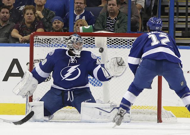 Tampa Bay Lightning goalie Ben Bishop (30) reaches for a shot as left wing Ryan Malone (12) moves in during the second period of an NHL hockey game against the Anaheim Ducks, Thursday, Nov. 14, 2013, in Tampa, Fla. (AP Photo/Chris O'Meara)