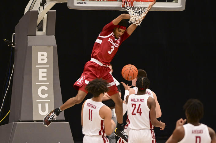 Stanford forward Ziaire Williams (3) hangs on the rim after dunking the ball as Washington State forward DJ Rodman (11) and guard Noah Williams (24) look on during the first half of an NCAA college basketball game, Saturday, Feb. 20, 2021, in Pullman, Wash. (AP Photo/Pete Caster)