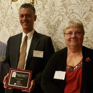 Ron Forsythe, Jr. Phd  CEO of Qlarant and Ms. Bonnie Horvath Program Director for Qlarant accept the Top Places to Work Award as a 3 time winner.