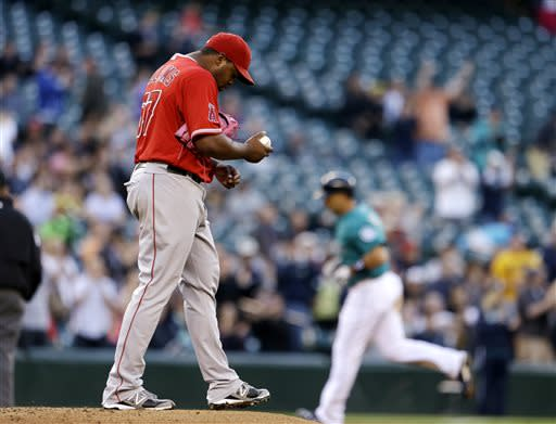 Los Angeles Angels starting pitcher Jerome Williams, left, turns away from the plate as Seattle Mariners' Raul Ibanez rounds the bases behind on a home run in the fourth inning of a baseball game Friday, July 12, 2013, in Seattle. (AP Photo/Elaine Thompson)