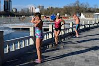 As the swimmers emerged from the lake, some doused themselves in warm water and watched the steam rise off their bodies