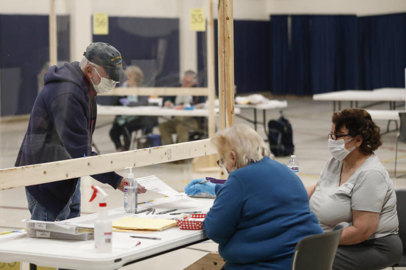A man checks in to cast his ballot at a Democratic presidential primary election at the Kenosha Bible Church gym in Kenosha, Wisconsin, on April 7, 2020.