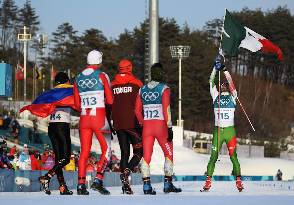 PYEONGCHANG-GUN, SOUTH KOREA – FEBRUARY 16: German Madrazo of Mexico holds the flag of Mexico as he crosses the finish line as Sebastian Uprimny of Colombia, Samir Azzimani of Morocco, Pita Taufatofua of Tonga and Kequyen Lam of Portugal look on during the Cross-Country Skiing Men's 15km Free event. (Getty Images)