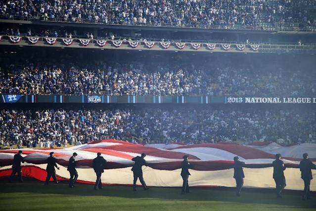 A giant U.S. flag is displayed during pre-game ceremonies prior Game 3 of the National League division baseball series between the Los Angeles Dodgers and the Atlanta Braves, Sunday, Oct. 6, 2013, in Los Angeles. (AP Photo/Jae C. Hong)