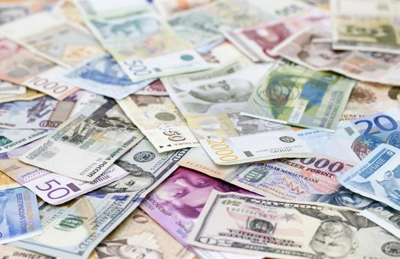 Pile of foreign currency spread out on a flat surface.