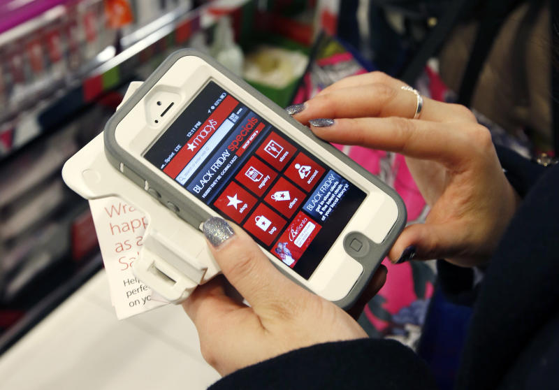 FILE - In this Friday, Nov. 23, 2012, file photo, Tashalee Rodriguez, of Boston, uses her smartphone while shopping at Macy's in downtown Boston. Facebook isn't just for goofy pictures and silly chatter. Whether shoppers know it or not, their actions online help dictate what's in stores during this holiday season. (AP Photo/Michael Dwyer, File)