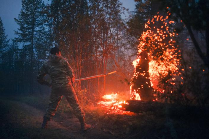 A member of volunteers crew mops up spot fires at Gorny Ulus area west of Yakutsk, Russia, Thursday, July 22, 2021. The hardest hit area is the Sakha Republic, also known as Yakutia, in the far northeast of Russia, about 5,000 kilometers (3,200 miles) from Moscow. About 85% of all of Russia's fires are in the republic, and heavy smoke forced a temporary closure of the airport in the regional capital of Yakutsk, a city of about 280,000 people. (AP Photo/Ivan Nikiforov)