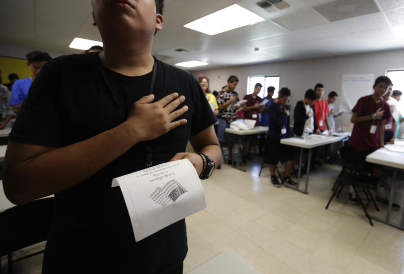 In this Tuesday, July 9, 2019, photo, immigrants say the Pledge of Allegiance in a writing class at the U.S. government's newest holding center for migrant children in Carrizo Springs, Texas. Following breakfast, children play soccer and then have classes held in trailers. (AP Photo/Eric Gay)