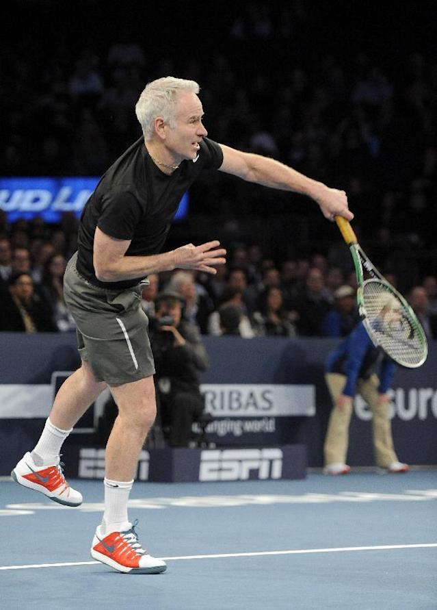 John McEnroe serves during his doubles match with his brother, Patrick against Mike and Bob Bryan in the BNP Paribas Showdown Tennis Tournament on Monday, March 3, 2014, in New York. (AP Photo/Kathy Kmonicek)