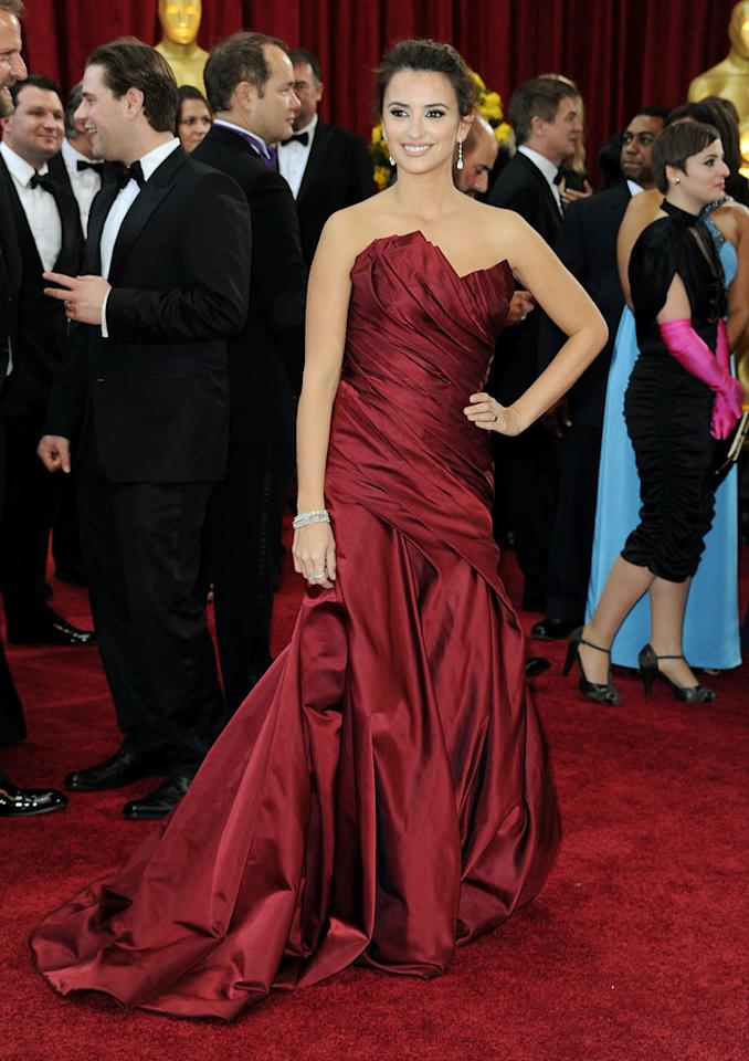 Penelope Cruz   Grade: A    The Spanish beauty was simply ravishing in a dusky red draped Donna Karan gown, chic bun, and Chopard jewels.
