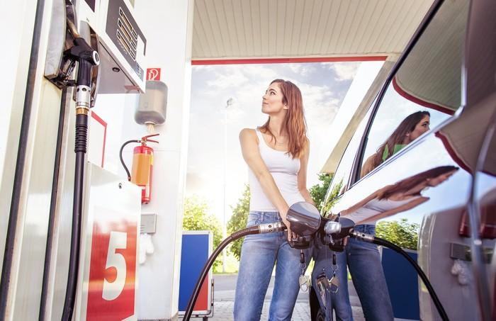 A young woman refuels her car at a gas station.