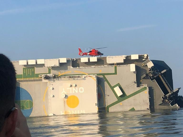 A US Coast Guard rescue helicopter sits on the overturned cargo ship MV Golden Ray off the coast of Georgia