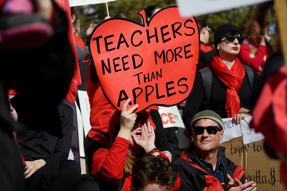 Munroe Elementary teacher Melissa Curry holds a sign during a rally across from the Colorado State Capitol as Denver public school teachers strike for a second day in Denver, Colorado, U.S., February 12, 2019. REUTERS/Michael Ciaglo